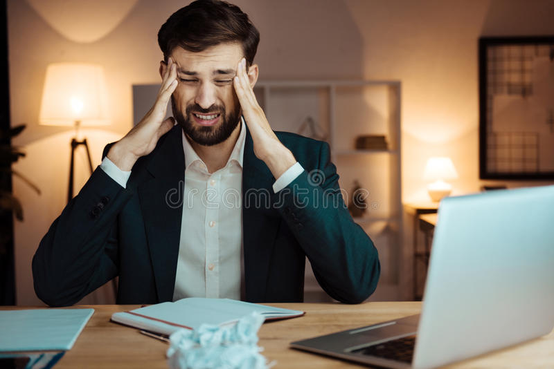 Tired man touching his forehead. I have headache. Concentrated office worker wrinkling forehead and putting elbows on the table while keeping eyes closed royalty free stock photo