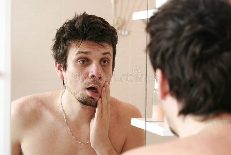 Tired man who has just woken up looks at his reflection in the mirror slaps his cheek with his hand. royalty free stock photo