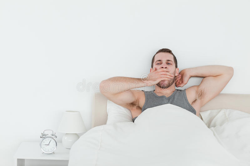 Tired man yawning while waking up. In his bedroom stock photos