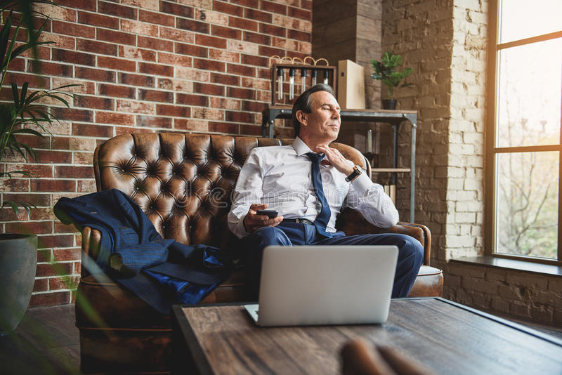 Tired mature businessman unleashing tie. Exhausted man is sitting on couch and untying necktie. He holding mobile stock image