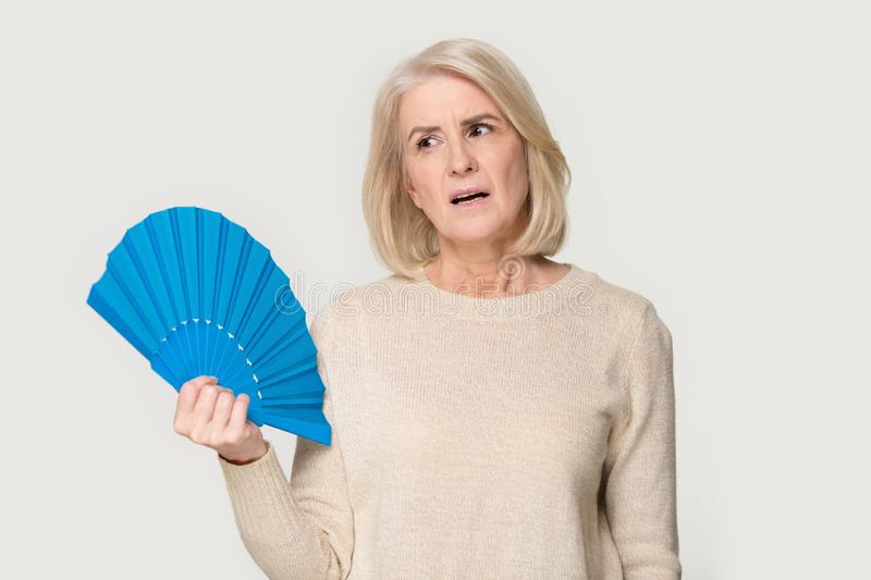 Overheated senior lady cooling herself using waver stock photos