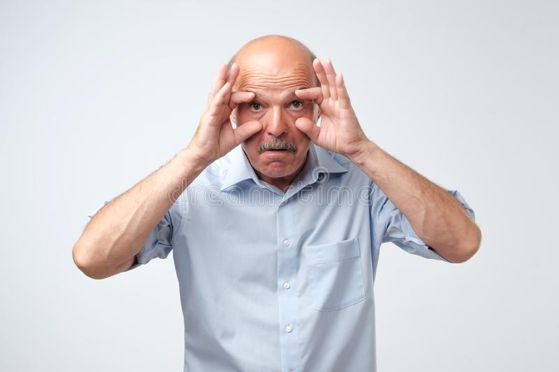 Tired mature man trying to open his eyes. He deadly wants to sleep, but has terrible insomnia. stock photo