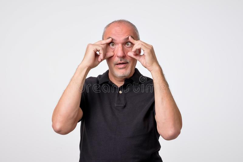 Tired mature man trying to open his eyes. He deadly wants to sleep, but has terrible insomnia. royalty free stock image