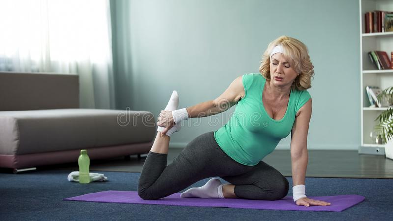 Tired mature woman doing yoga exercises, stretching legs, healthy lifestyle stock image