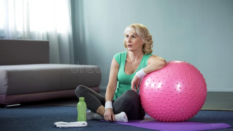 Tired mature woman sitting on mat resting after workout, leaning on fitball royalty free stock photos