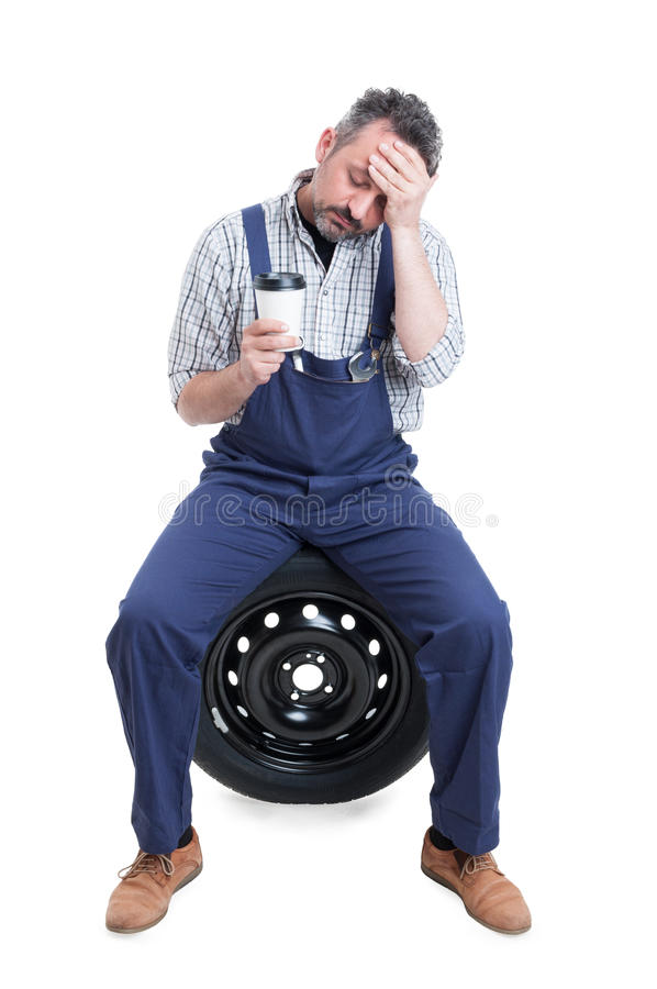 Tired mechanic sitting on tire and drinking coffee stock image