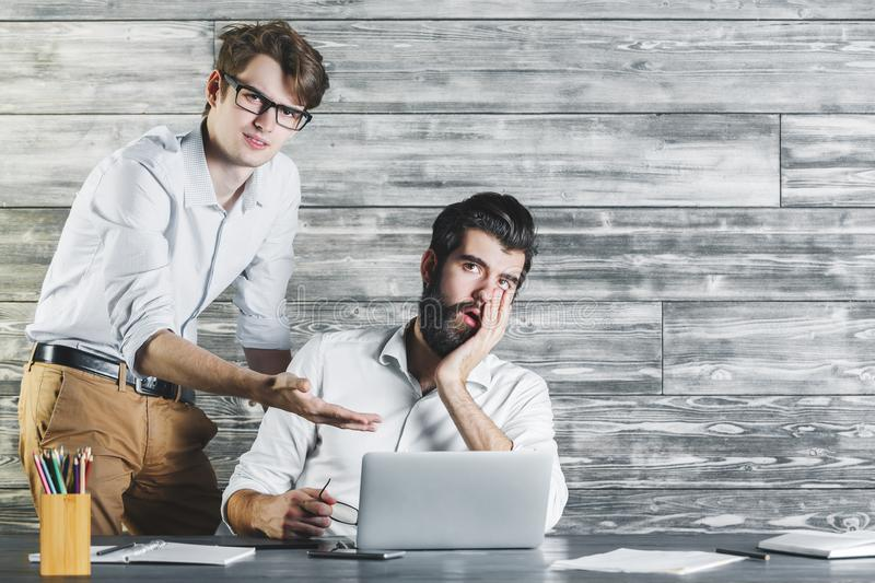 Tired men using laptop. Two tired men using laptop and discussing something at modern office desk with wooden wall in the background. Technology, project stock photo