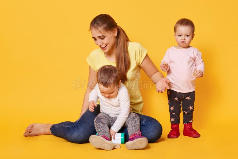 Tired merry woman plays with her active funny kids being on maternity leave. A young cheerful woman enjoys spending time within royalty free stock image
