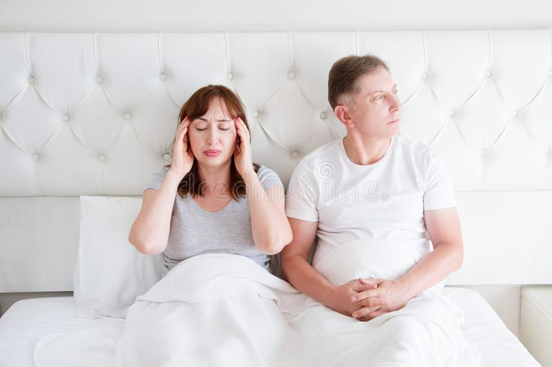 Tired middle age family couple in bed. Woman feel pain and migraine in head. Strong tension headache and stress concept. Copy stock image