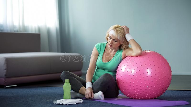 Tired middle aged female relaxing on yoga mat after active home workout, dyspnea stock image
