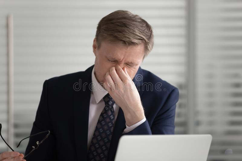 Tired middle aged male manager suffering from dry eyes syndrome. stock photo