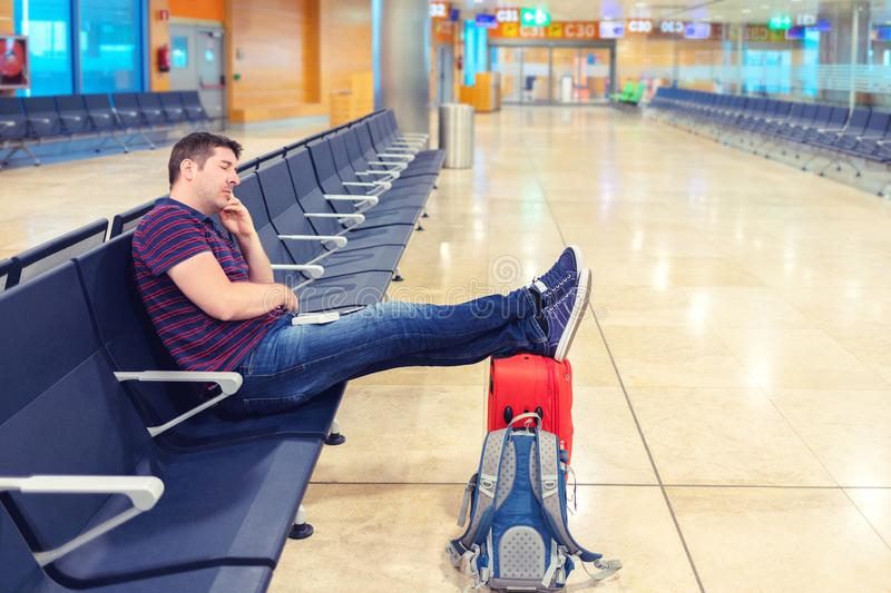 Tired middle aged man sleeping with legs on suitcase in departure hall in airport stock photo