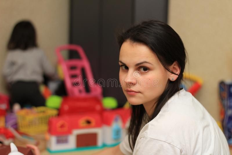 Tired mom on the background of children& x27;s toys. Mess, mother, room, house, mum, untidy, woman, kids, exhausted, everywhere, home, many, stressed royalty free stock images