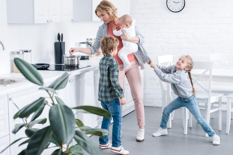 tired mother holding infant child and cooking while naughty children playing vector illustration