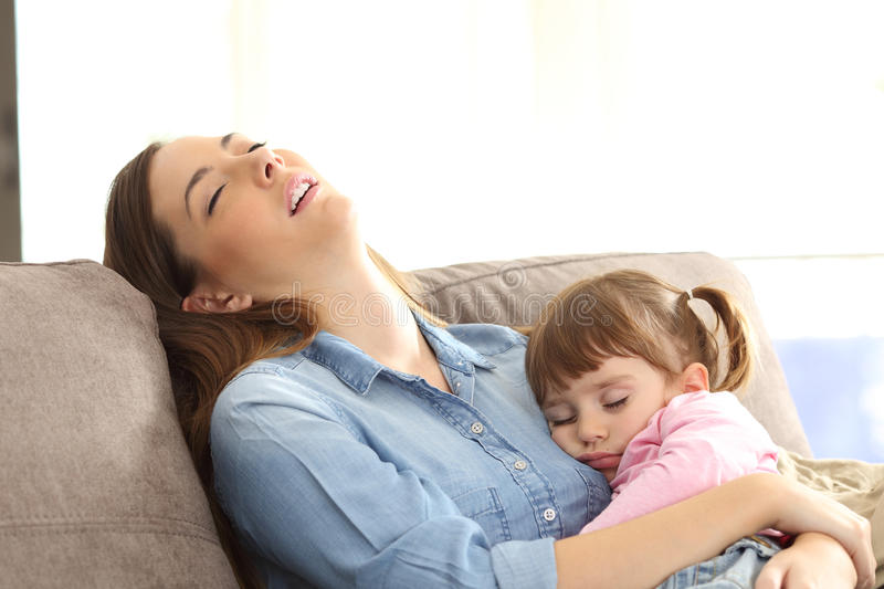 Tired mother sleeping with her baby daughter. Tired mother sleeping embracing to her asleep baby daughter sitting on a sofa at home royalty free stock image