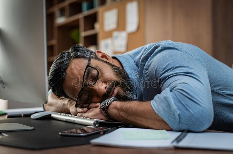 Tired businessman sleeping on computer desk. Tired multiethnic businessman sleeping in office. Middle eastern business man with eyeglasses worked late and fell stock photo