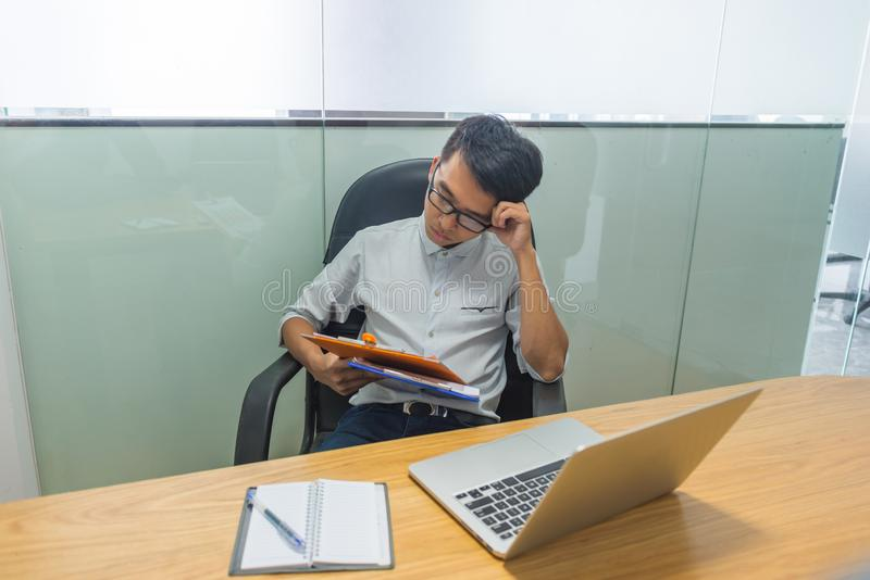 Tired office man feel worried about financial number on report stock photography