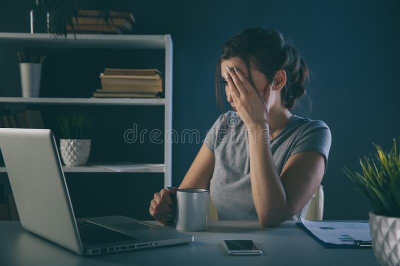 Tired office woman at her desk infront of computer. royalty free stock photo