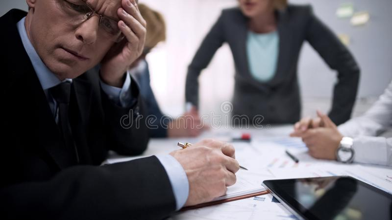 Tired office worker feeling scared, suffering at meeting with terror lady boss stock photos