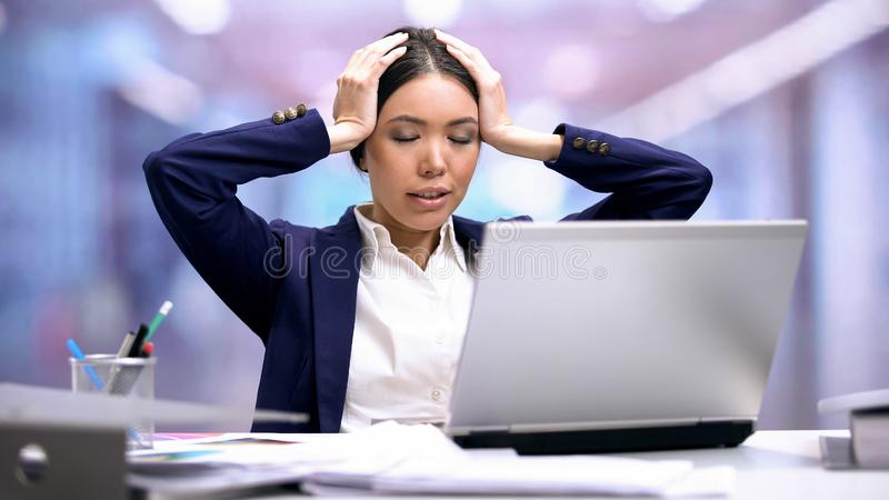 Tired office worker sitting front of laptop, overwork stress, deadline anxiety royalty free stock image