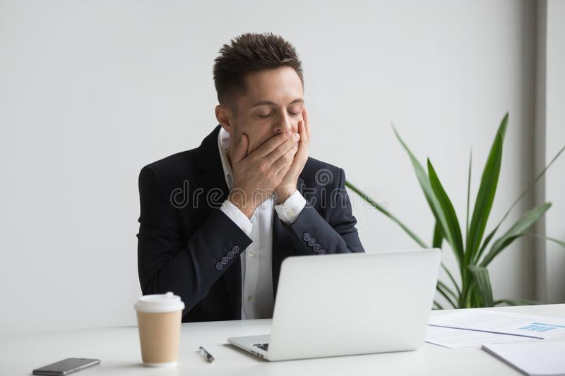 Tired office worker yawning working long hours stock images