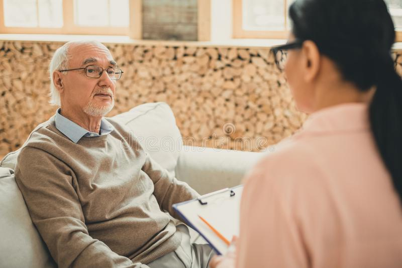 Tired old man resting on the couch and looking on his volunteer. Important conversation. Tired old men resting on the couch and looking on his female volunteer royalty free stock photo