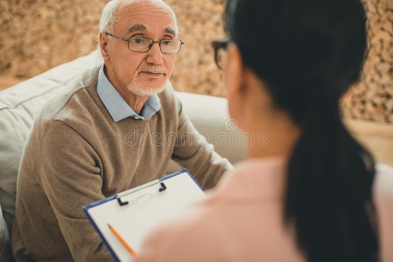 Senior with grey hair directly looking on dark-haired woman. Tired old man. Senior with grey hair directly looking on dark-haired women during meeting about his royalty free stock photos