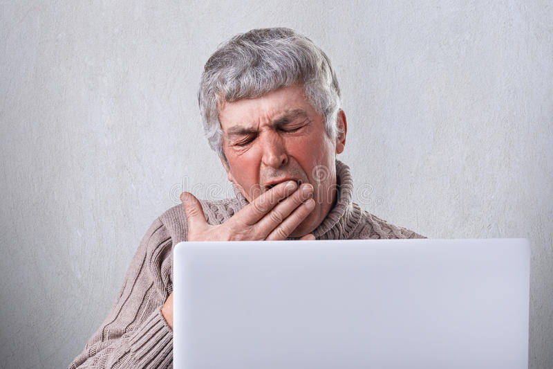 A tired old man yawning in frot of his laptop being fatigued while after writing his book. A mature man with gray hair holding his stock image