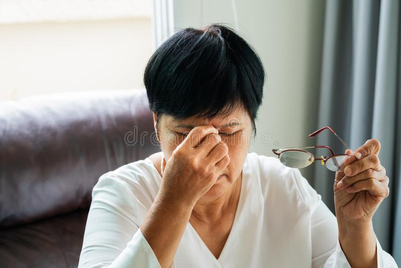 Tired old woman removing eyeglasses, massaging eyes after reading paper book. feeling discomfort because of long wearing glasses royalty free stock image