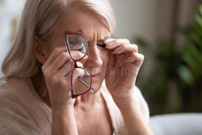 Tired older woman taking off glasses, feeling eye strain stock photography