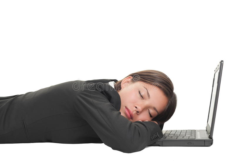Tired overworked business woman. Sleeping on her laptop being exhausted from work, Beautiful mixed race Chinese Asian-Caucasian young businesswoman isolated on royalty free stock photo