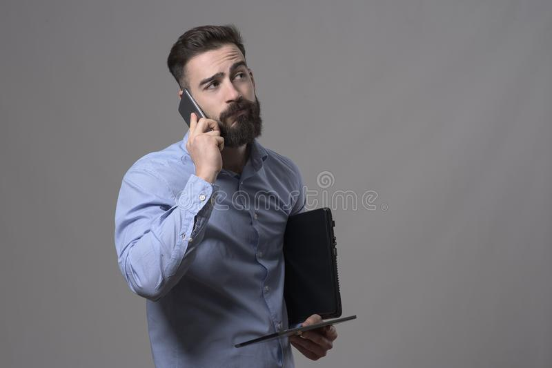 Tired overworked man on the phone holding laptop and tablet computer looking away royalty free stock photo