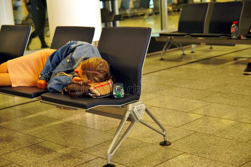 Tired passenger sleeping on a bench in airport terminal after flight cancellation. flight get late, stock image