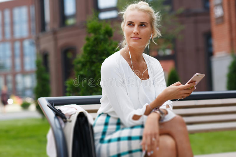 Tired pensive young woman leaning on sculpture outdoors royalty free stock photography