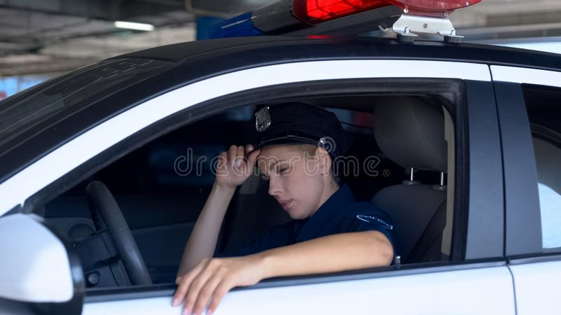 Tired police woman adjusting hat, sitting in squad car, exhausted sub work. Stock photo stock images