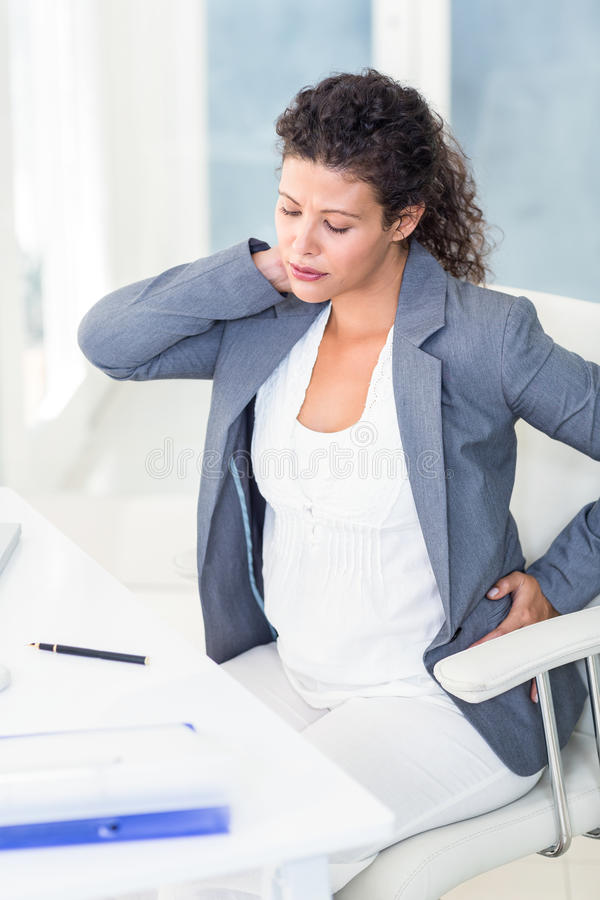 Tired pregnant businesswoman stock images
