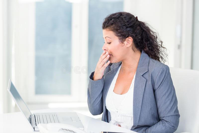 Tired pregnant businesswoman yawning stock images