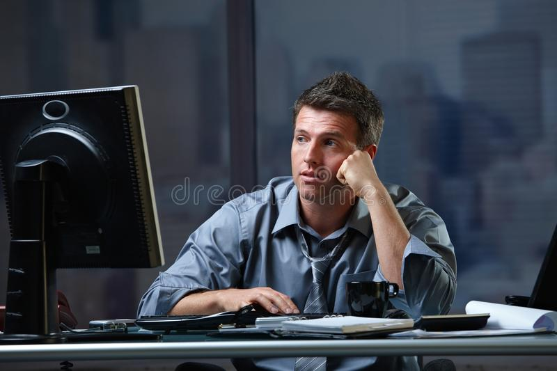 Tired professional looking at screen troubled. Tired professional businessman looking at computer screen troubled, thinking at office desk working overtime royalty free stock photos