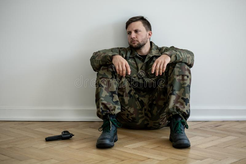 Tired professional soldier in green uniform sitting on the floor next to a gun royalty free stock images
