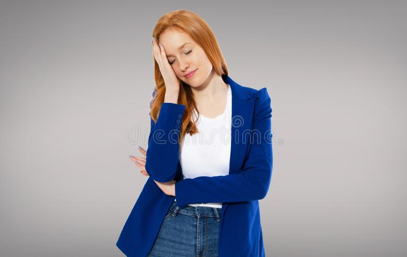 Tired red-haired girl holds her head with a migraine head - girl woman head ache, head pain stock photography
