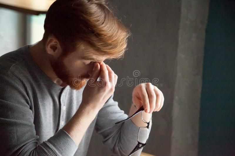 Tired millennial man massaging nose feeling fatigue from work. Tired red haired man take glasses off working too long at computer, exhausted millennial male stock photography