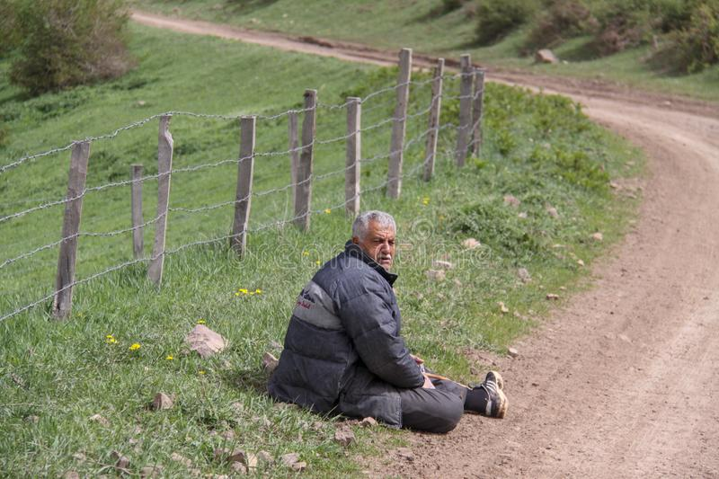 A tired rural man sitting next to the road on the floor, A farm is enclosed with a fence, Iran, Gilan royalty free stock image