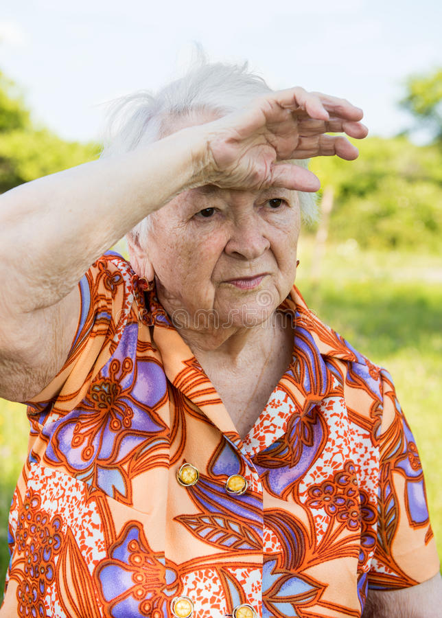 Tired sad old woman. On nature background royalty free stock photos