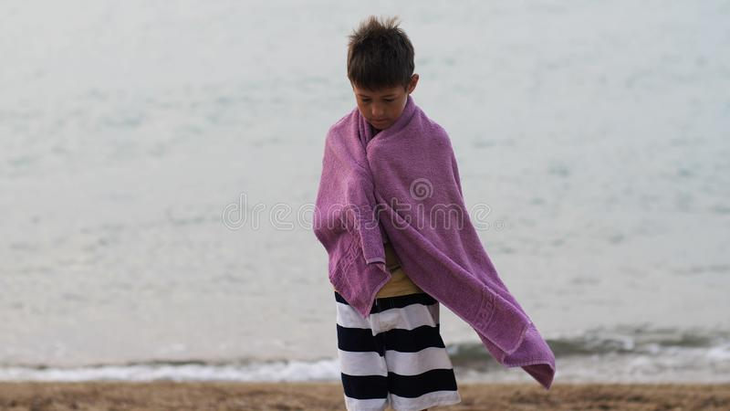 Tired sad refugee boy in a towel stands alone looking into the camera, boy is trying to keep warm. Have fun royalty free stock images