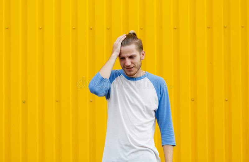 Tired, sad student man holding his head on a yellow background. Stress concept. Copy space. stock photos