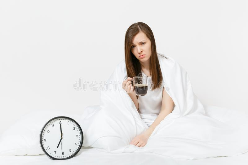Tired sad woman sitting in bed with cup of coffee, round clock, white sheet, pillow, wrapping in blanket on white stock images