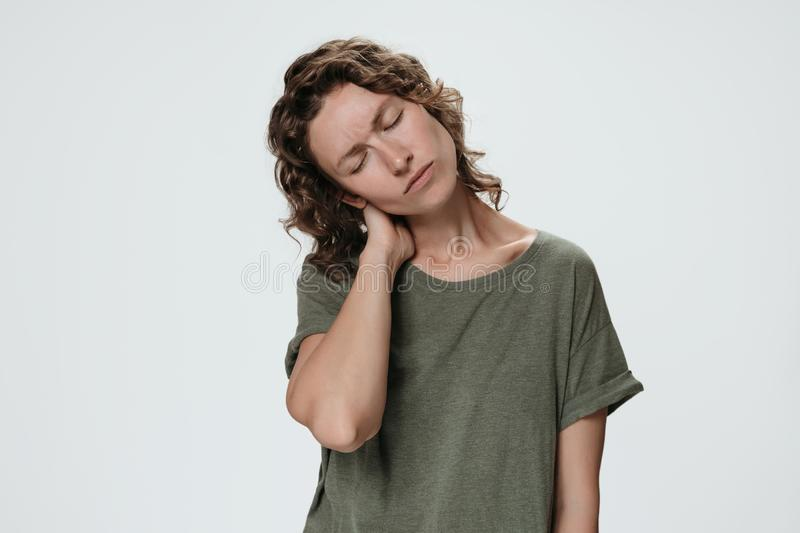 Tired sad young caucasion woman suffering from fatigued massaging hurt stiff neck royalty free stock photo