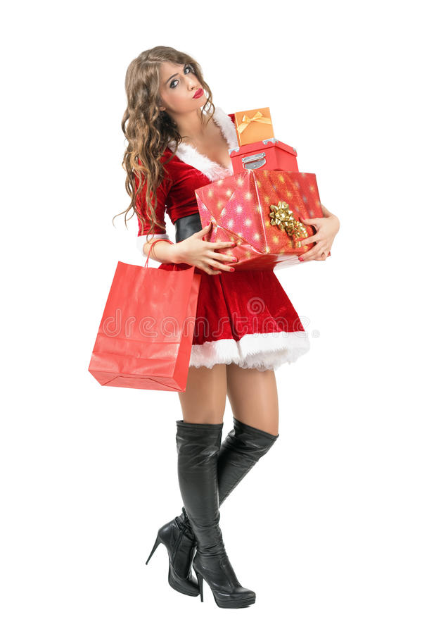 Tired Santa woman carrying many gift boxes looking at camera. Full body length portrait isolated over white studio background stock photography