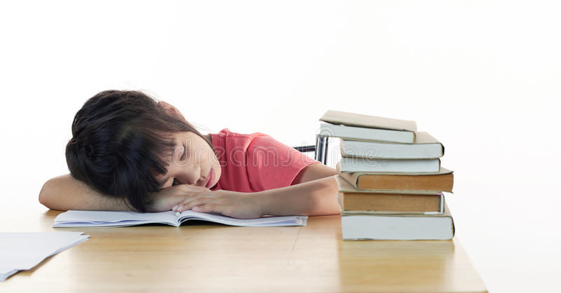 Tired schoolgirl sleeps at the desk stock images