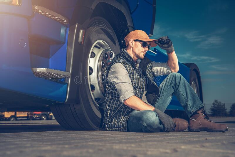 Truck Stop Relaxing. Tired Semi Truck Driver Seating on a Truck Stop Parking Pavement Next to His Tractor Vehicle stock image